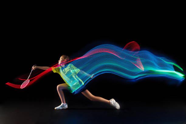 un adolescent caucasien fille femme jouant joueur de Badminton sur fond noir - Photo