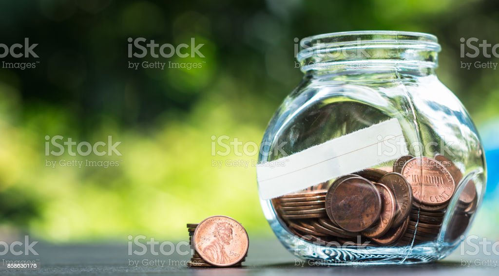 one cent coins in a glass jar on the table in a garden stock photo