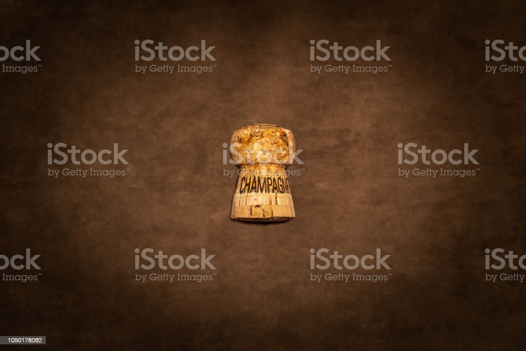 One champagne cork with text against brown suede texture seen from above. stock photo