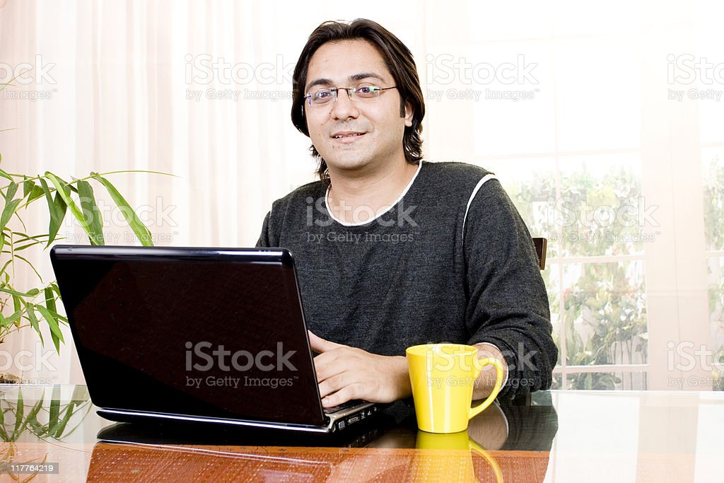 One Cheerful Indian Businessman Using Laptop royalty-free stock photo