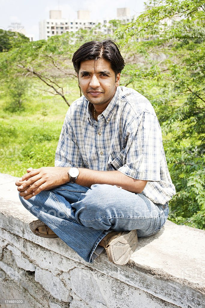 One cheerful Indian youth sitting outdoor stock photo