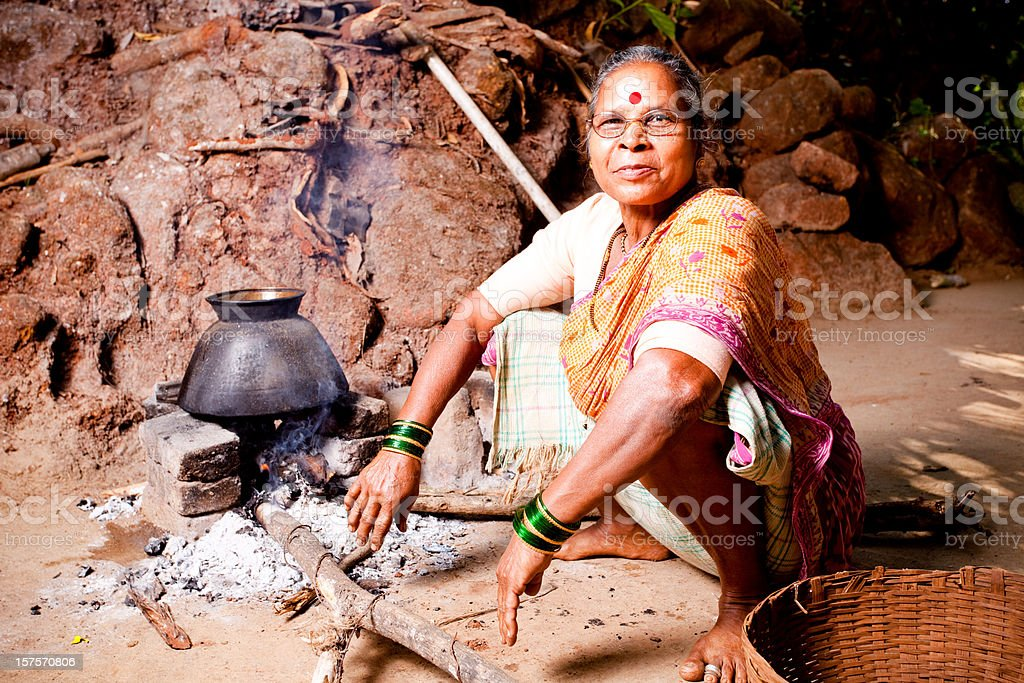 One Cheerful Rural Indian Woman sitting and preparing food Horizontal royalty-free stock photo