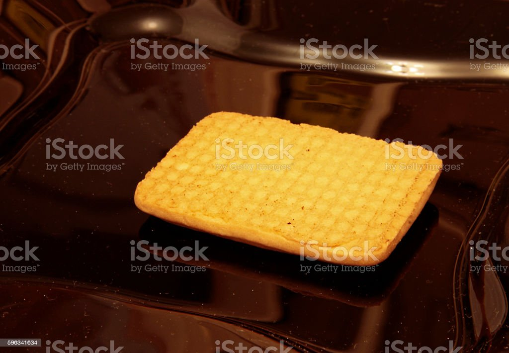 One cookie laying on the black plate Lizenzfreies stock-foto