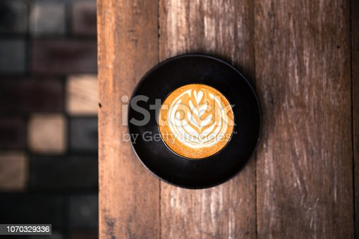 One cup of cappuccino with beautiful latte art on wooden background. Top view.