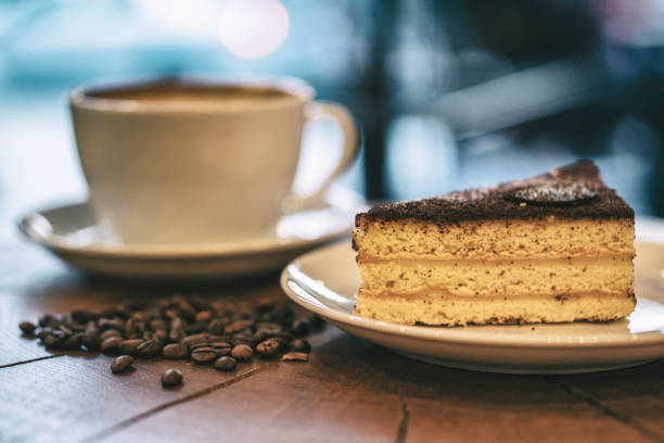 one cup of espresso and piece of cake on a wooden board - cake foto e immagini stock