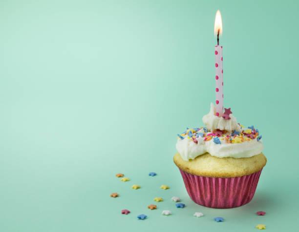 ein cupcake mit brennenden kerze und sterne streusel auf grünem hintergrund isoliert - einladungskarten kindergeburtstag stock-fotos und bilder