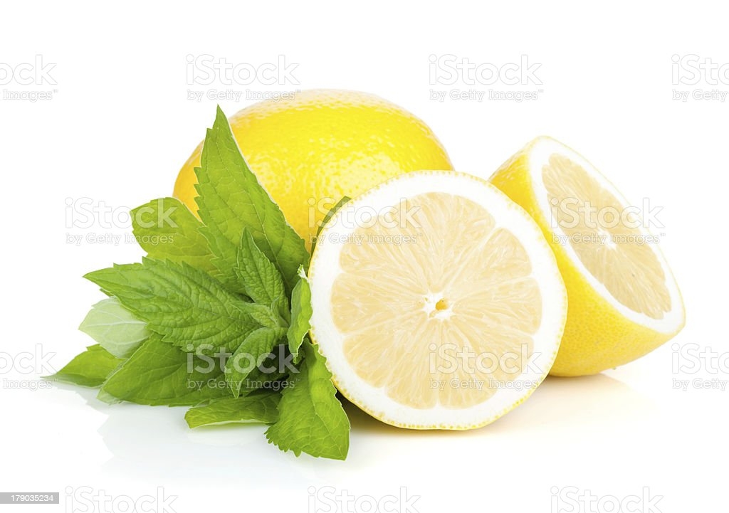 One cut and uncut lemon with mint against a white background royalty-free stock photo