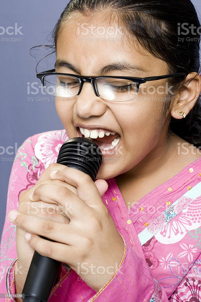 One Cute Little Indian girl singing holding Microphone stock photo