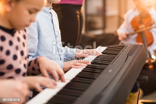 Young woman's hand playing the piano, teaching boy and a girl to play at the same time