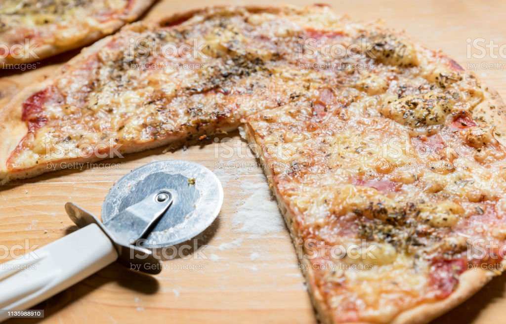 One domestic pizza with circle cutter knife on the wooden table...