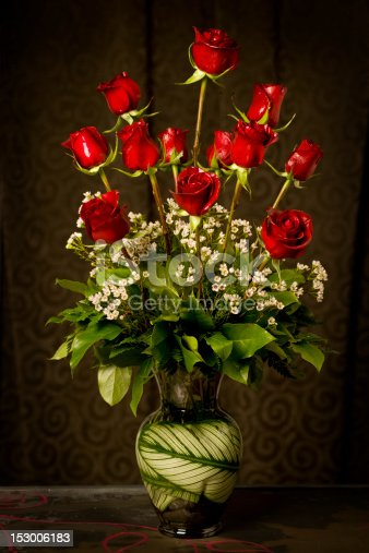An elegant arrangement of a dozen red roses, with some small white flowers as accent in a glass vase.