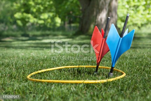 a shot of some vintage lawn darts somtimes called JARTS. One of each  color inside the yellow ring in a back yard setting.