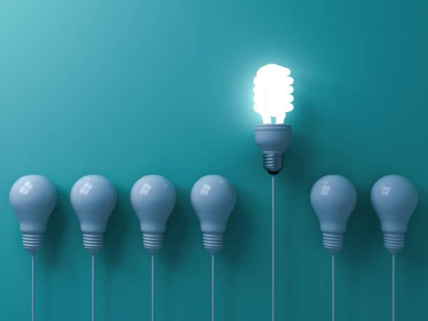 uma lâmpada de luz brilhando e se destacando do apagado incandescentes brancos na liderança de fundo de parede de cor verde pastel e renderização em 3d ideia criativa diferentes conceitos poupança de energia de eco - habilidade - fotografias e filmes do acervo