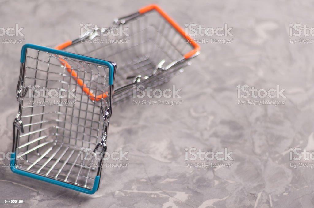 One empty metal glossy market basket with blue handles near chrome...