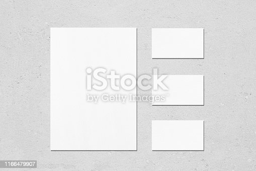 1173565159 istock photo One empty white vertical a4 sized poster and three horizontal rectangle business card mockups 1166479907