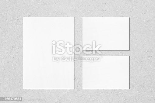 1171907064 istock photo One empty white vertical a4 sized poster and two a5 sized horizontal rectangle card mockups 1166479851