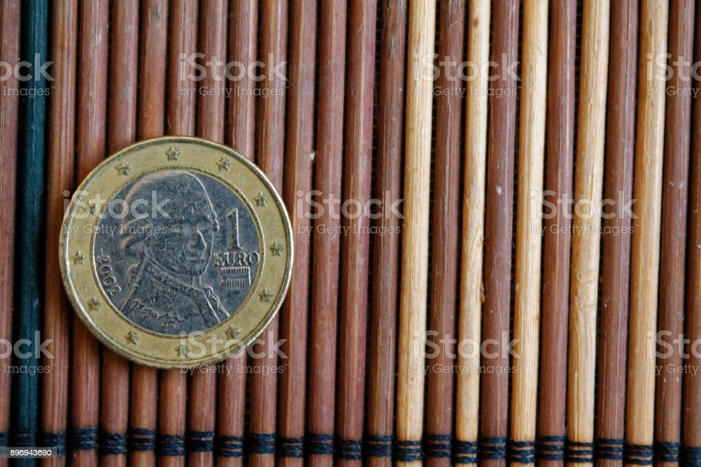 One euro coin lie on wooden bamboo table Denomination is 2 euro - back side stock photo