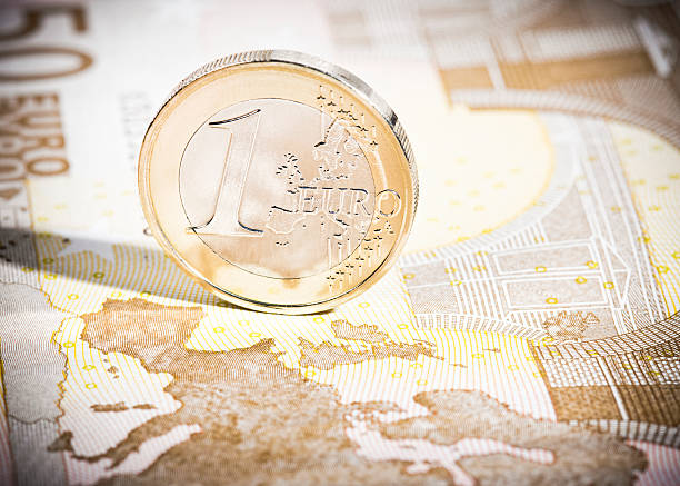 One Euro coin on €50 note map macro A clean 1 Euro coin reflecting the map of Europe printed on the 50 Euro banknote. european union coin stock pictures, royalty-free photos & images