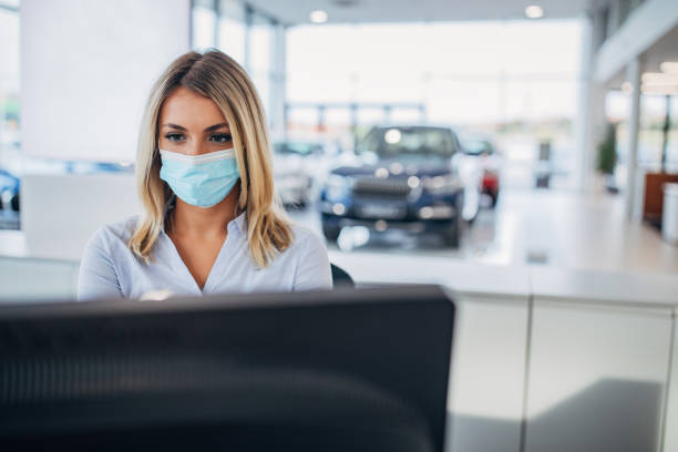 One female car dealer with protective face mask working on computer in car showroom