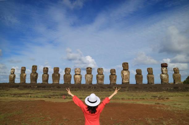 ein weibchen, hob die arme freudig vor moai statuen der ahu tongariki auf der osterinsel, chile, südamerika - osterinsel stock-fotos und bilder
