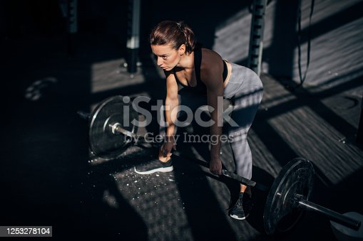 One fit young woman weightlifting with barbell in the gym.