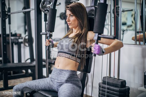 One young fitness woman exercising on exercise machine for arms