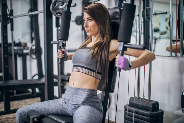 One fitness woman exercising on exercise machine for arms stock photo