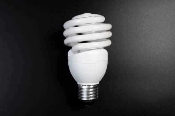 One fluorescent light bulb in the dark room on black background for energy saving concept. One fluorescent light bulb in the dark room on black background for energy saving concept. Energy saving light bulb for thinking idea. canadian football league stock pictures, royalty-free photos & images