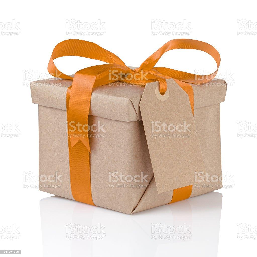 Un regalo di Natale in scatola con avvolgimento di carta e fiocco arancione - foto stock