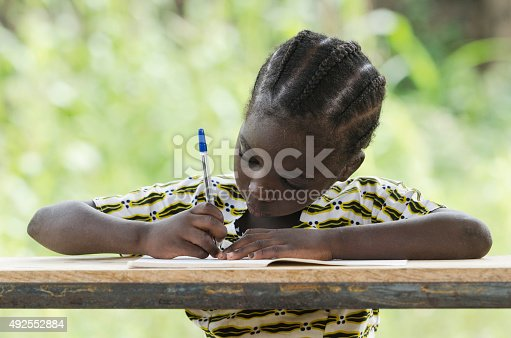 istock One Girl Only: Little African Girl Writing in her Workbook 492552884