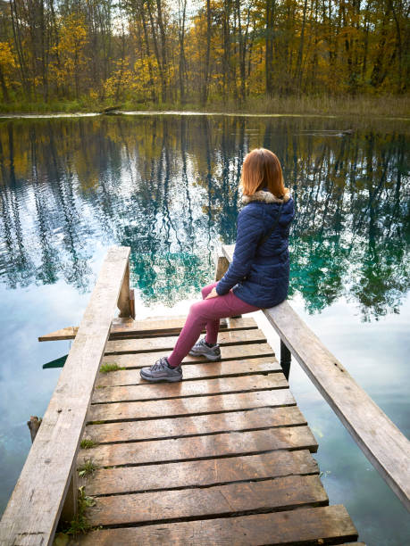 one girl sit on wooden old pier - forest bathing foto e immagini stock