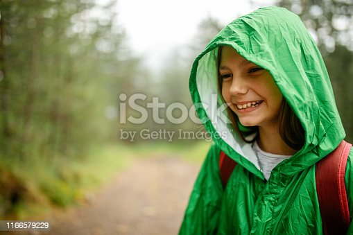One cute girl hiking in nature at rain season and wearing green raincoat. She is very happy and positive
