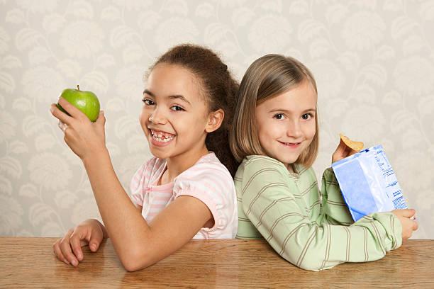 ein mädchen und ein apfel und ein mädchen mit einer packung von chips - kinder verpackung stock-fotos und bilder