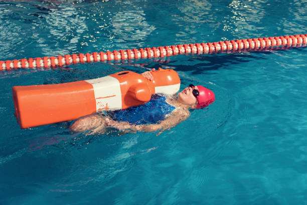 One Girl with Training Dummy in a Pool One Girl with Training Dummy in a Pool lifeguard stock pictures, royalty-free photos & images
