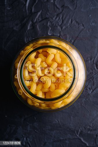 istock One glass jar with cavatappi uncooked golden wheat curly pasta on textured dark black background, top view 1224151826