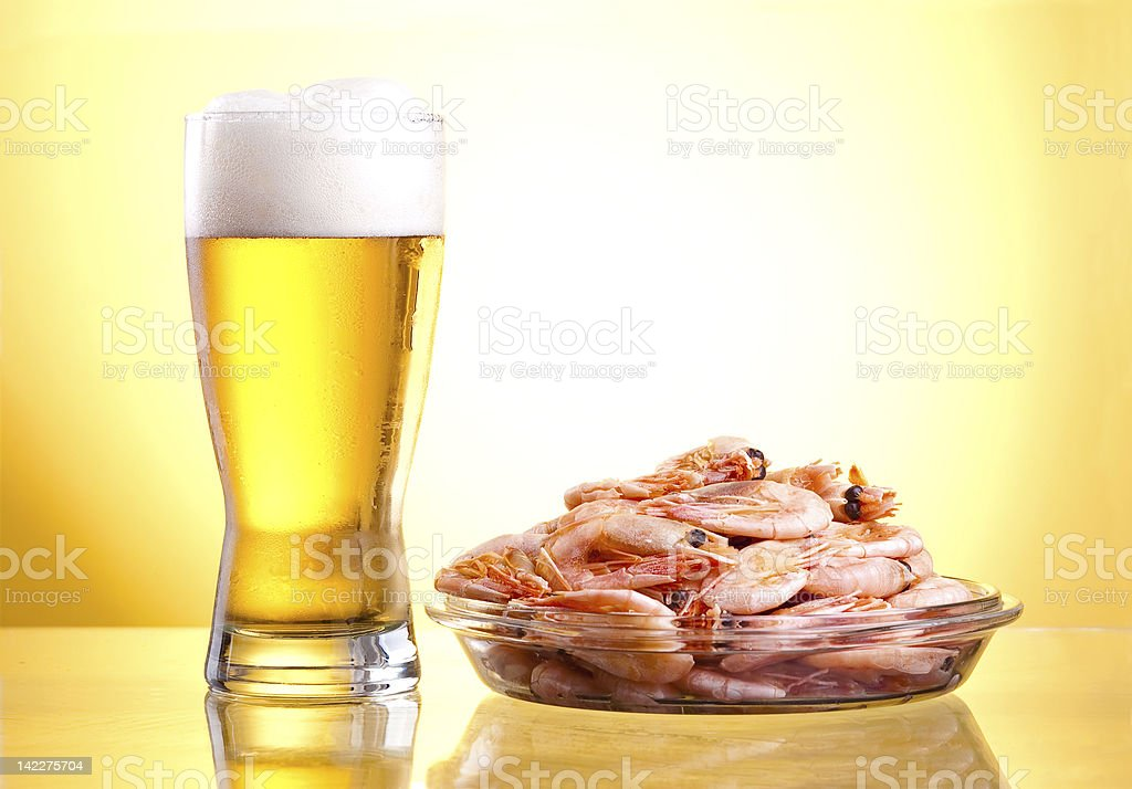 One glass of beer and cooked shrimp on a plate royalty-free stock photo