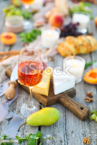 istock One glass of rose wine on table with fruits and cheese 856675386