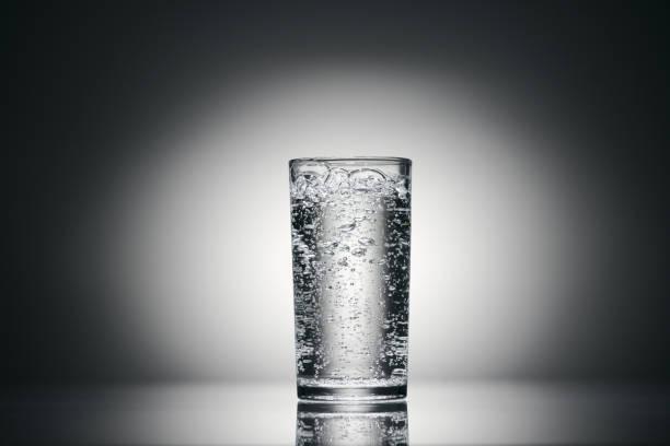 un vaso de agua con gas sobre un fondo oscuro - foto de stock