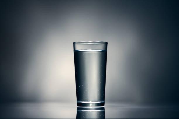 un vaso de agua sobre un fondo oscuro - foto de stock