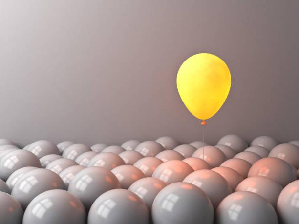 ein glühender ballon wie mond, der in der dunklen nacht über anderen düsteren ballons über weißem hintergrund mit fensterreflexionen erstrahlt - individualität stock-fotos und bilder