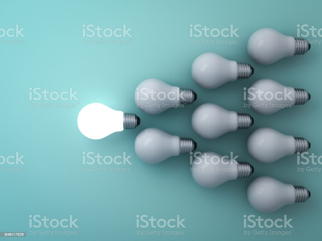 One glowing light bulb standing out from the unlit incandescent bulbs on green background leadership and different concept stock photo