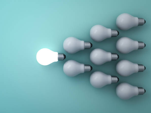 one glowing light bulb standing out from the unlit incandescent bulbs on green background leadership and different concept - lead stock photos and pictures