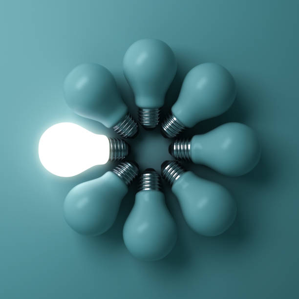 One glowing light bulb standing out from the unlit incandescent bulbs on green background with shadow , individuality and different creative idea concepts stock photo