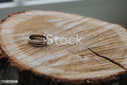 istock One gold wedding ring lying on the wooden stump cut. Close-up. Focus on the ring, the background is blurred. 1149228409