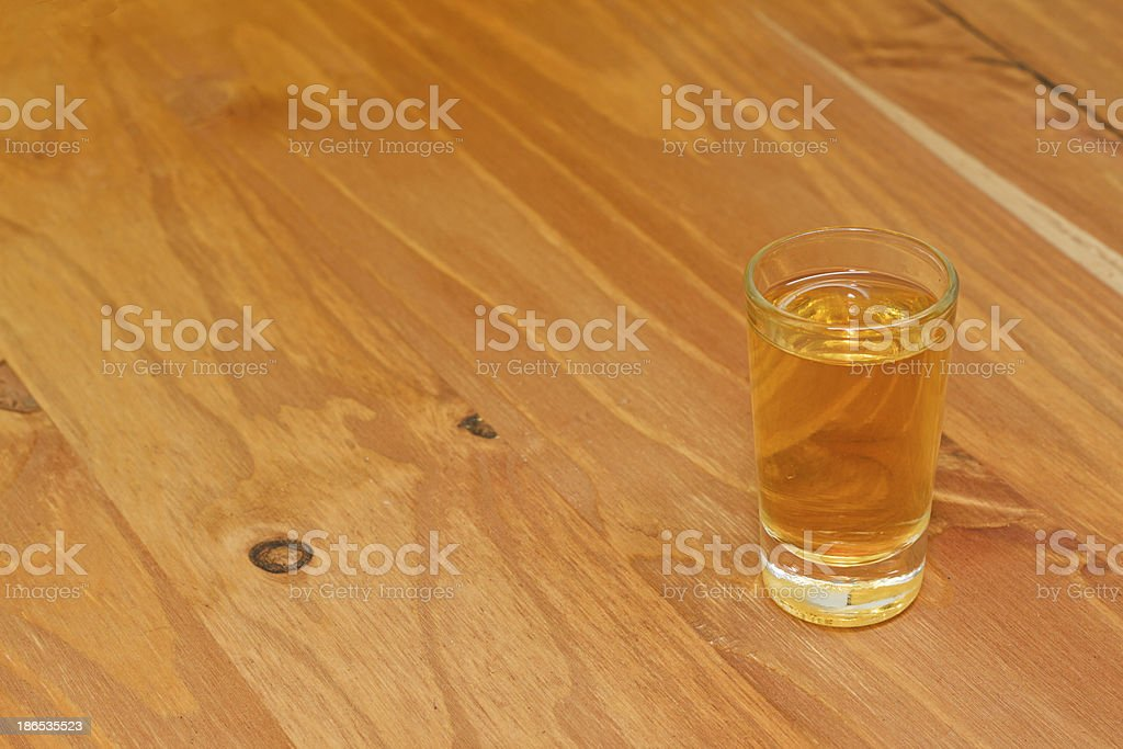 One golden homemade herbal liqueur shot on wooden background stock photo