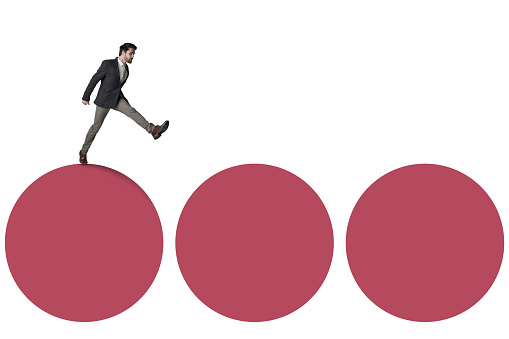 Shot of a businessman waking across three circles against a white background
