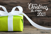 istock One Green Gift, White Bow, Wooden Background, Merry Christmas And A Happy 2021 1277102450