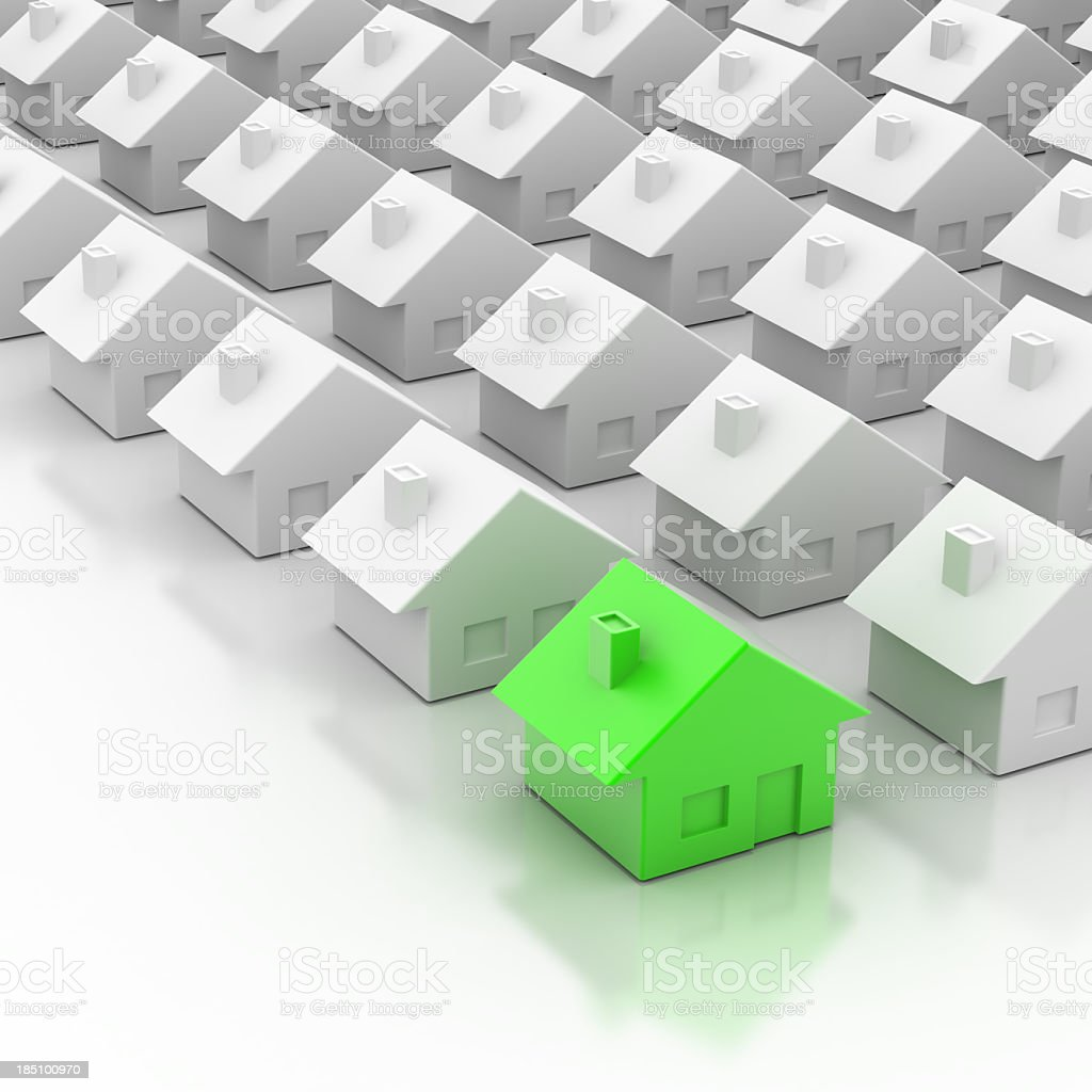One green miniature house in a group of ordinary white homes stock photo