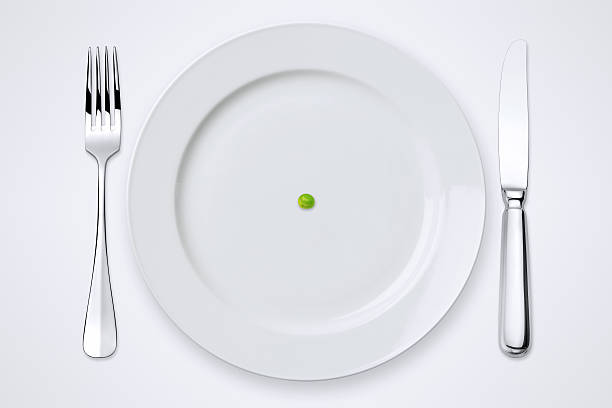 one green pea on plate. table setting with clipping path. - tabak stok fotoğraflar ve resimler