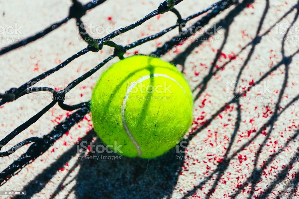 One green tennis ball on court, sport competition concept. Tennis net...